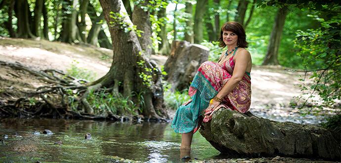 Natascha Schlienz sitzt im Wald an einem See
